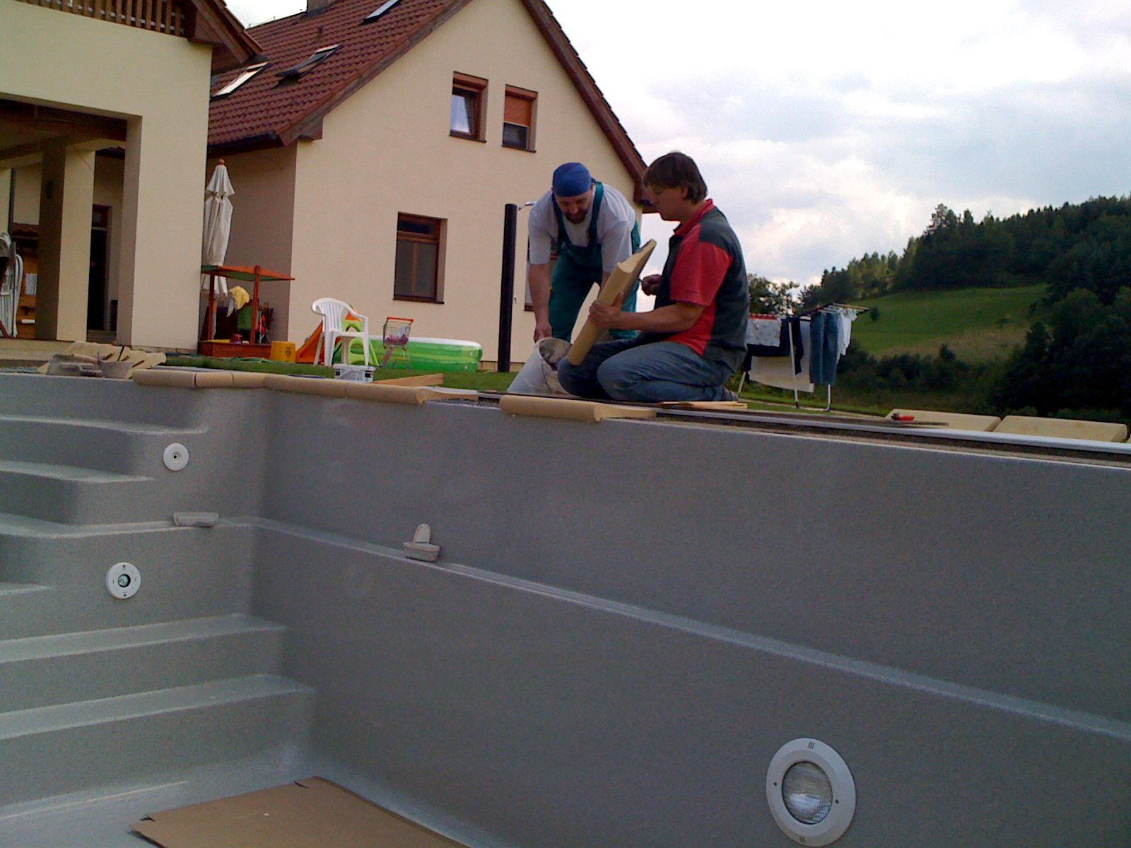 laying the ceramic edge of the pool